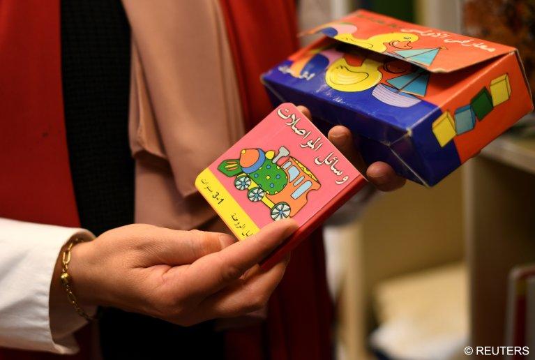كتاب أطفال باللغة العربية  بين يدي أخصائية اجتماعية نور تعمل  في مشروع لإدماج المهاجرين في برلين/  الصورة: رويترز / أنجريت هيلس