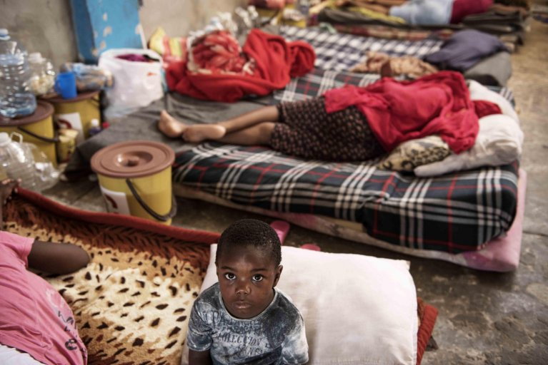 A child sits on a mattress laid on the floor of the women's section of the Al-Nasr detention center in Zawiya, Libya | Photo: ANSA/UNICEF