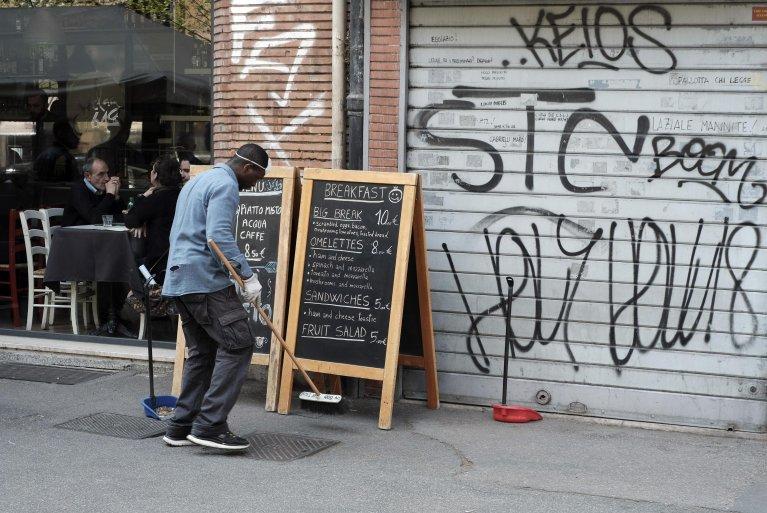 """ansa / مهاجر من وسط أفريقيا ينتظر الحصول على """"تصريح عمل وإقامة"""" في إيطاليا، يقوم بتنظيف الرصيف أمام أحد مطاعم روما مجانا. المصدر: صورة من أرشيف أنسا."""