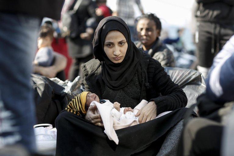 ANSA / مهاجرة تحمل طفلاً رضيعاً بعد أن هبطت من العبارة باروس جيت، لدى وصولها من جزيرة ساموس إلى ميناء أليفسينا قرب أثينا. المصدر: إي بي إيه/ كوستاس تسيرونيس.