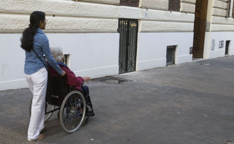 A home carer accompanies her elderly employer on a walk in Rome | PHOTO: ANSA