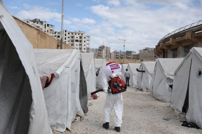 "ANSA / متطوعون من منظمة ""البنفسج"" المحلية غير الحكومية يرتدون أمتعة الحماية الشخصية، ويقومون بعملية تعقيم في إدلب. المصدر: إي بي إيه / يحيى نعمة."
