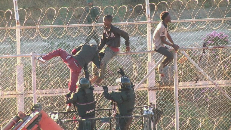 Migrants attempting to climb the barbed wire fence between Morocco and the Spanish enclave of Ceuta | Photo: Reuters