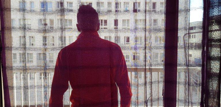 Achour qui vient de fêter ses 18 ans entouré de son éducatrice et de sa psychologue se tient devant la fenêtre de son studio à quelques minutes à pieds de la gare Saint-Charles à Marseille. Crédit : Anne-Diandra Louarn / InfoMigrants