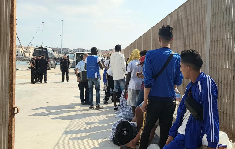 """المهاجرون الذين كانوا على متن السفينة """"أوبن آرمز"""" بعد هبوطهم في لامبيدوزا. المصدر: أنسا / إليو ديسيديرو."""