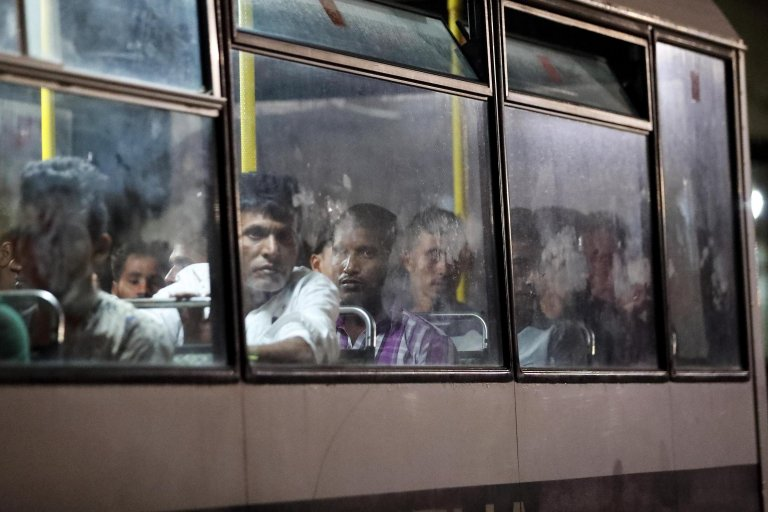 Migrants are driven away on police buses after disembarking on Malta in September 2019 | Photo: EPA/Domenic Aquilina