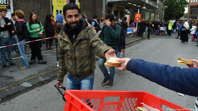 A refugee is handed food after he arrives in Dortmund | Photo: Getty Images/AFP/P.Stollarz