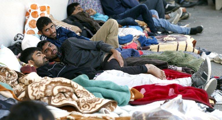 مهاجرون من آسيا وشمال أفريقيا يجلسون وينامون في حديقة، بسبب نقص أماكن الإقامة في مدينة توزلا البوسنية. المصدر: إي بي إيه/ فهيم دامير