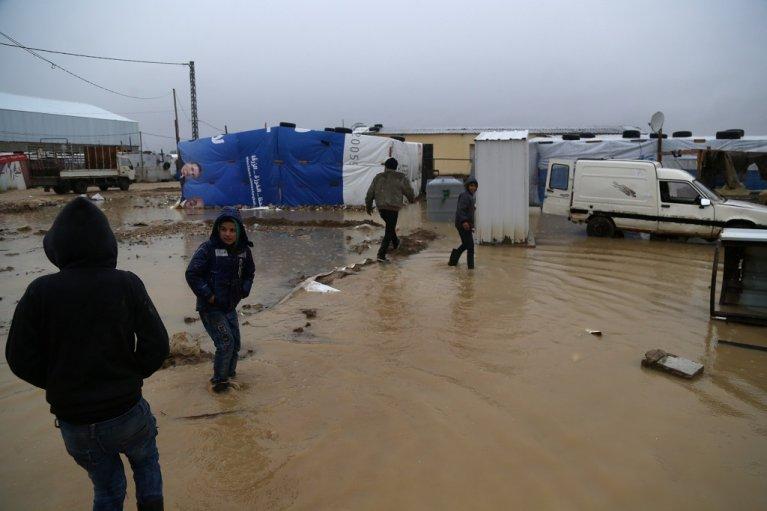 أطفال يلهون بالقرب من خيامهم في مدينة بر الياس شرق لبنان، وتظهر السيول وقد اجتاحت المخيم عقب العاصفة القطبية التي ضربت البلاد خلال الأيام الماضية. رويترز