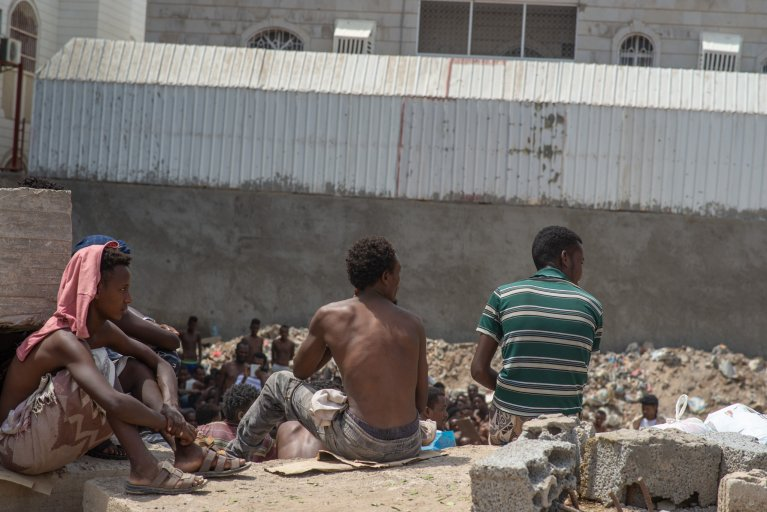 From file: A group of Ethiopian migrants stranded in Aden city sit on cement blocks while they and their fellow migrants surrounding them pray to return home to Ethiopia | Photo: IOM 2020/Rami Ibrahim