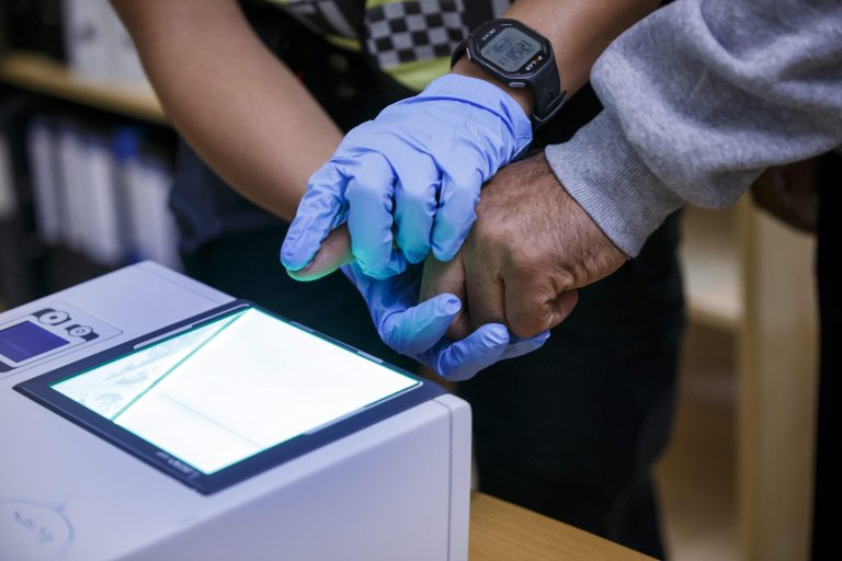 The picture shows a police officer taking fingerprints of a refugee in the Police Immigration office in Svinesund, Norway: EPA, Archive