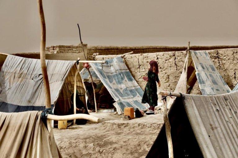 یوه بې ځایه شوې میرمن افغانستان په مزار شریف کې د IDP په یو کمپ کې د اوبو د جوشلو لپاره اور چمتو کوي. انځور:  UNHCR