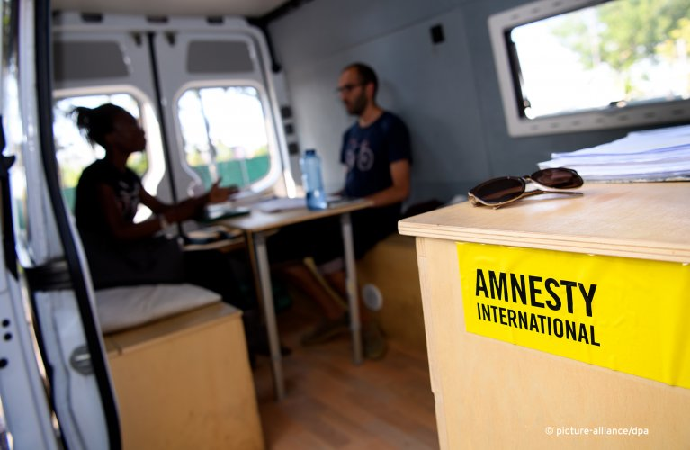 "Aydin Alinejad of the Munich Refugee Council is talking to a woman from Uganda in the ""Infobus for Refugees"" 