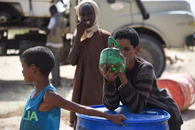 Malian repatriated refugees drink water from a plastic container in the Timbuktu Region of Mali   PHOTO: EPA/NICOLAS REMENE