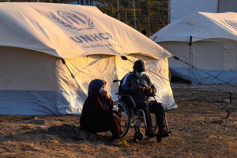 A woman and a man in a wheelchair sitting outside a tent in the Kara Tepe camp, Lesbos, Greece   Photo: ARCHIVE/EPA/VANGELIS PAPANTONIS