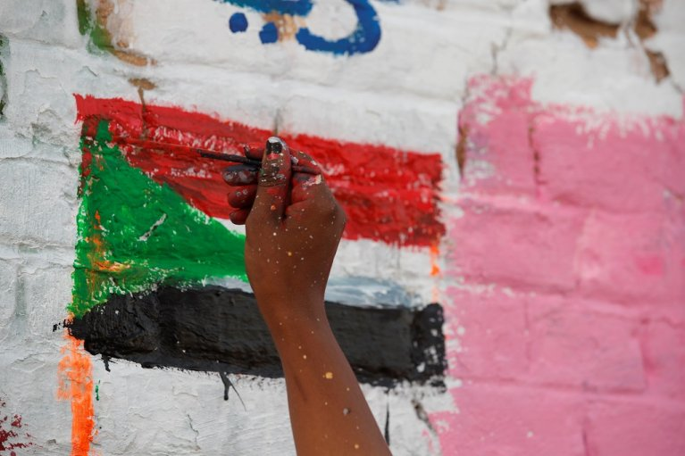 A hand paints the Sudanese flag on a wall | Photo: InfoMigrants
