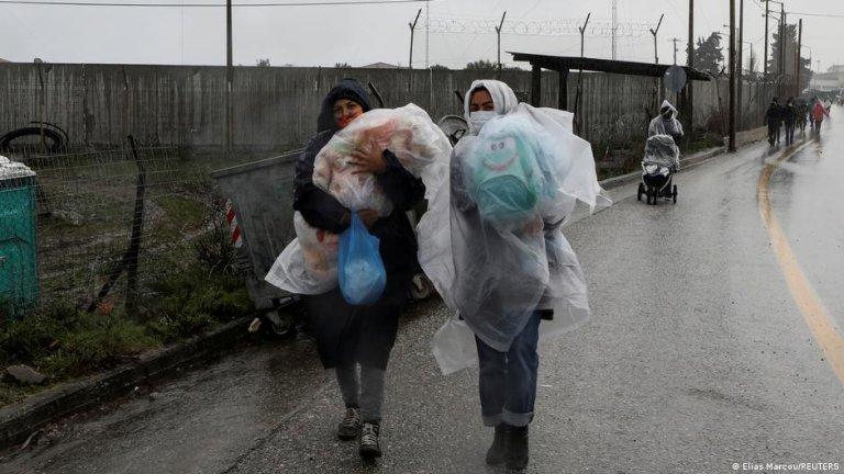 زنان مهاجر افغان جلوی اردوگاه کاراتیپه در جزیره لیسبوس نوزدان شان را برای محافظت از باران درپلاستیک پیچانده اند