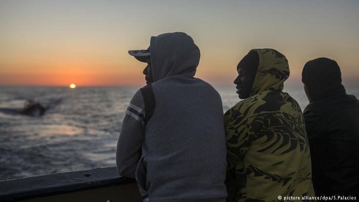 Three migrants staring out at the Mediterranean from the ship that rescued them (picture alliance/dpa/S.Palacios)