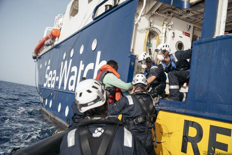 Les équipes du Sea-Watch 4 aident des personnes secourues à monter à bord. Crédit : Fabian Melber/Sea-Watch