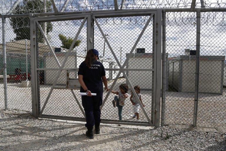 """صورة توضيحية """"أرشيف""""، طفلان عراقيان خلف سياج في مركز أميغداليزا لترحيل المهاجرين في أثينا. المصدر: إي بي إيه / يانيس كولسيديس، انسا."""