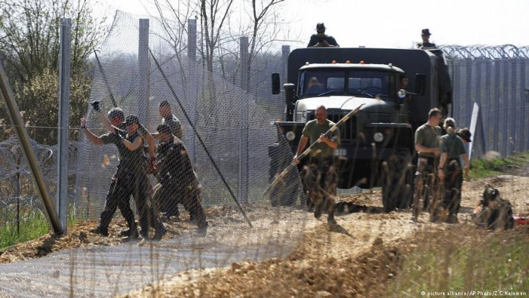 Hungarian army soldiers build a temporary fence on the border with Serbia