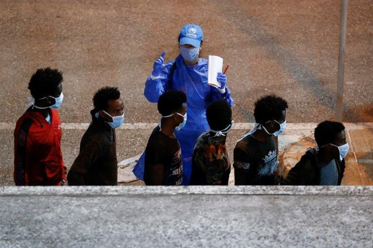 أحد عناصر فريق مفوضية اللاجئين يتفقد المهاجرين لحظة إنزالهم في ميناء فاليتا، عاصمة مالطا. الإثنين 27 تموز\يوليو 2020. رويترز