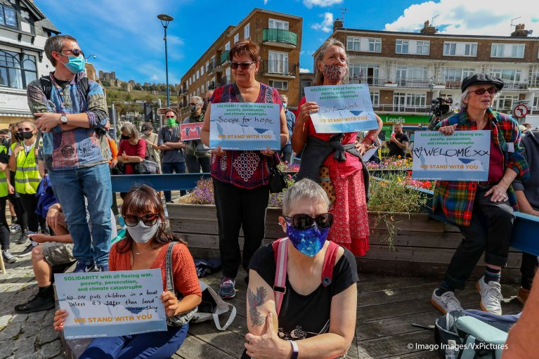 People wearing face protective masks holding pro-refugees and migrants placards are gathered in Market Square, in Dover on Saturday, Sept 5, 2020 | Photo: IMAGO