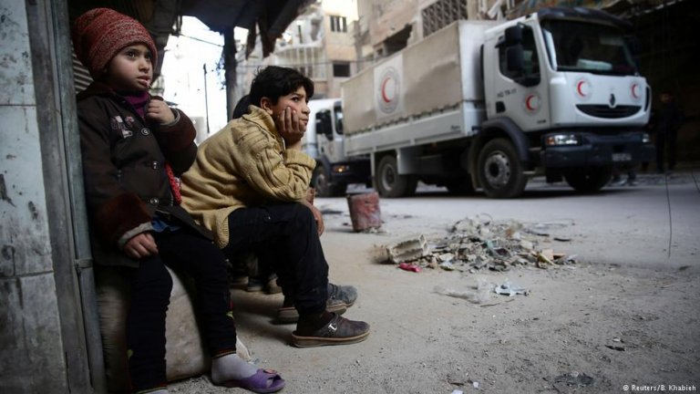 a boy and a girl sit down in the rebel enclave of east Ghouta