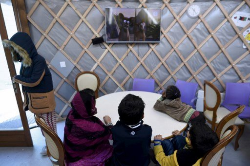 LIONEL BONAVENTURE / AFP  Des enfants migrants regardent la télévision dans une salle commune du centre d'Ivry-sur-Seine, en banlieue parisienne, février 2017 (illustration).