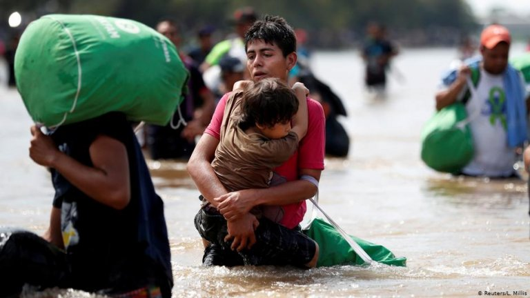 A young man holds a child while crossing a river on their way to the US | Photo: Reuters/L.Millis