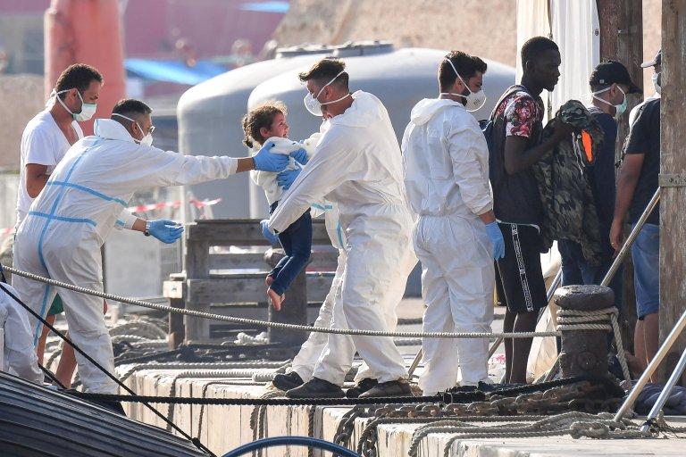 ANSA / فحص درجة حرارة مهاجرين أثناء عملية هبوطهم عقب وصولهم إلى جزيرة لامبيدوزا قادمين من شمال أفريقيا. المصدر: أنسا / أليساندرو دي مايو.