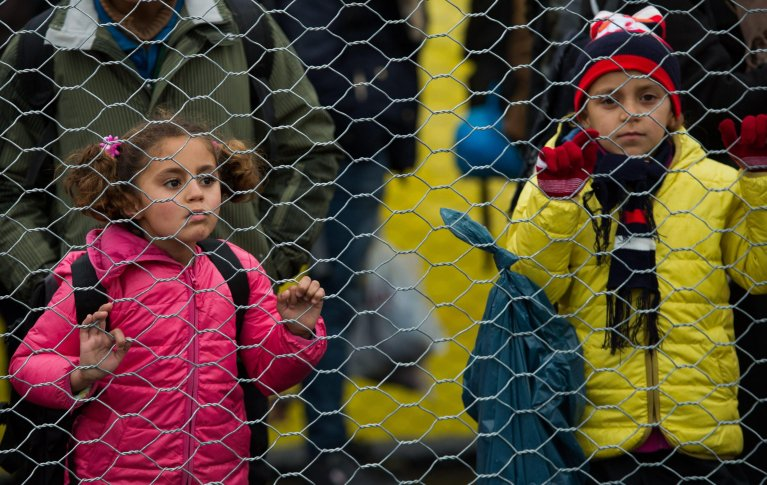 Migrant children line up as they walk along a border fence after they crossed the Slovenian-Austrian border, near the village of Spielfeld, Austria, 16 February 2016 | Photo: EPA/CHRISTIAN BRUNA