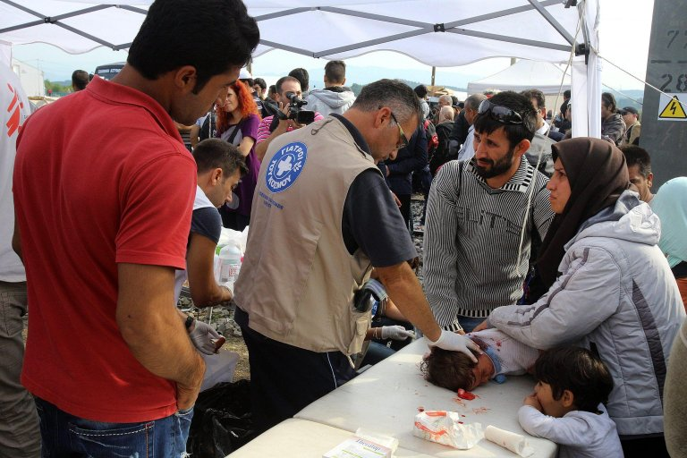 A doctor giving fist aid to an injured baby at a migrant camp in Greece   Photo: EPA/NIKOS ARVANITIDIS
