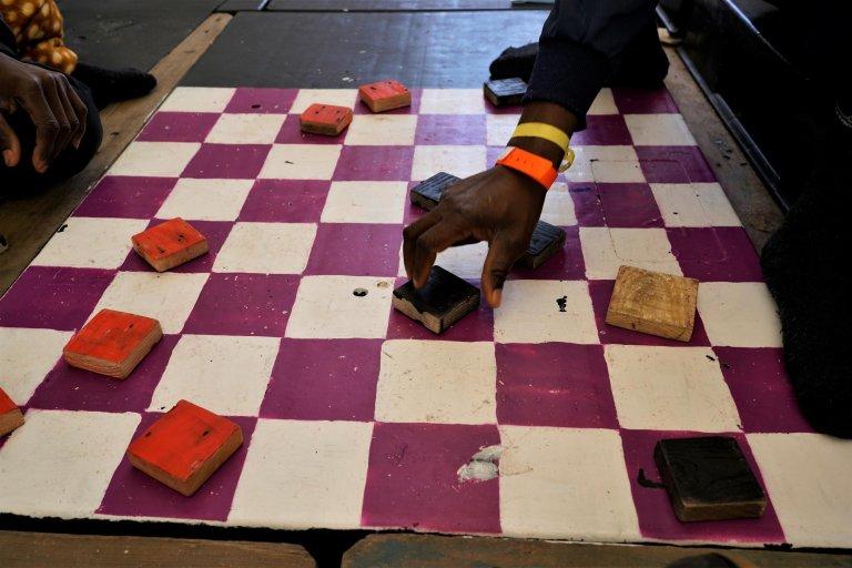 © RFI/Guilhem Delteil |Devant l'abri des hommes, deux damiers peints sur le sol sont une distraction prisée pour occuper le temps.
