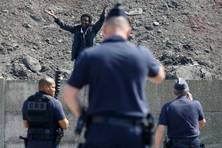 Des policiers et des migrants à Calais, dans le nord de la France. Crédit : Reuters