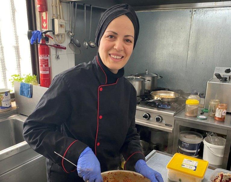 اللاجئة السورية  راما عبد الغني تساعد في تحضير وجبات للعاملين في المجال الصحي