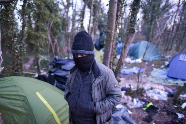 This man stands in front of the migrant camp near Verrotières in Calais. (Credit: Mehdi Chebil)