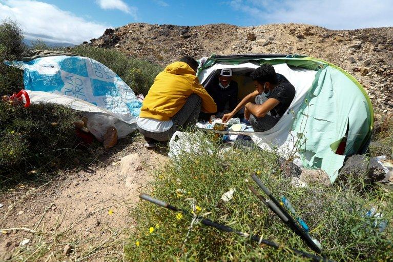 مهاجرون يأكلون داخل إحدى الخيم التي أقيمت على سفح جبل مطل على ساحل مدينة لاس بالماس في جزيرة غران كناريا، بعد أن طردوا من مركز إيواء يديره الصليب الأحمر في المدينة. 5 آذار/مارس 2021. رويترز