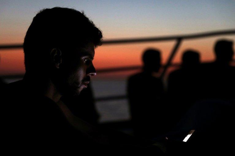 REUTERS/Yannis Behrakis |Un migrant cherche à joindre sa famille à bord du navire de l'ONG espagnole « Proactiva Open Arms » alors qu'ils rejoignent le port de Trapani en Sicile.