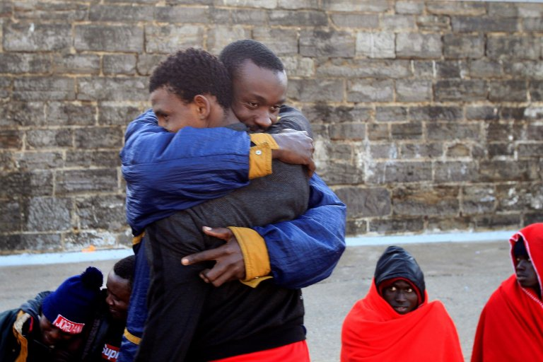 Two Sub-Saharan migrants embrace each other as they wait for their Transfer after they were rescued at sea
