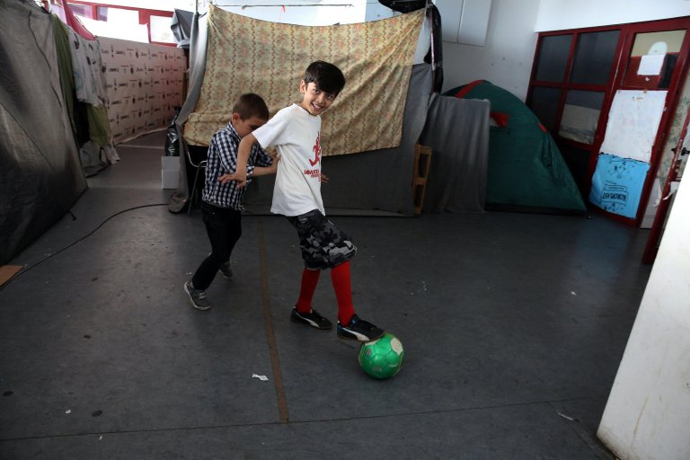 In the picture children play football in the refugee camp of the former Olympic Complex in Athens Credit: EPA/SIMELA PATZARTZI