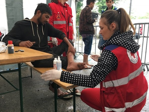 Red Cross workers look after the health of migrants in Bosnia, some of whom have allegedly received injuries from the Croatian police Credit: InfoMigrants