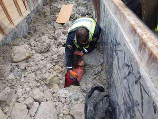 پولیس مهاجران را در یگ واگون از زیر خاک و گل بیرون میآورد. عکس از پولیس نوو مستو