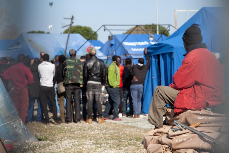 Farmhands around a tent where a migrant died in a fire in the tent camp managed by Catholic charity Caritas in San Ferdinando in Calabria | ANSA/M. Costantino