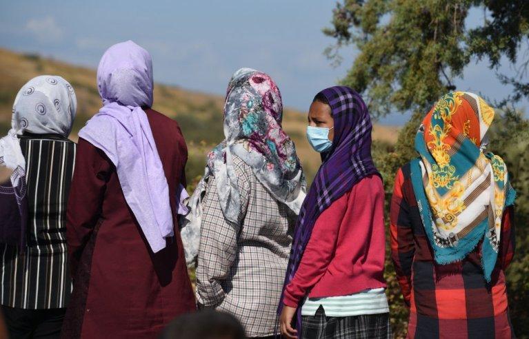 یک زن مهاجر که در صف توریع غذا ماسک به صورت دارد. عکس از  مهدی شبیل/ مهاجر نیوز