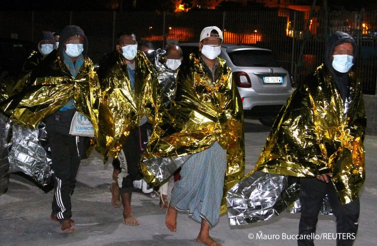 Migrants walk, wrapped in emergency thermal blankets, after arriving by the hundreds on the southern island of Lampedusa, Italy May 9, 2021 | Photo: Mauro Buccarello / REUTERS