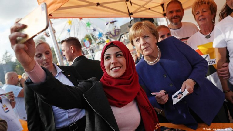 Chancellor Angela Merkel taking a selfie with a woman in a headscarf