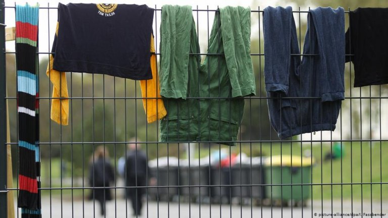 Clothing hangs on a fence at a refugee shelter | Photo: Picture-alliance/dpa/I.Fassbender