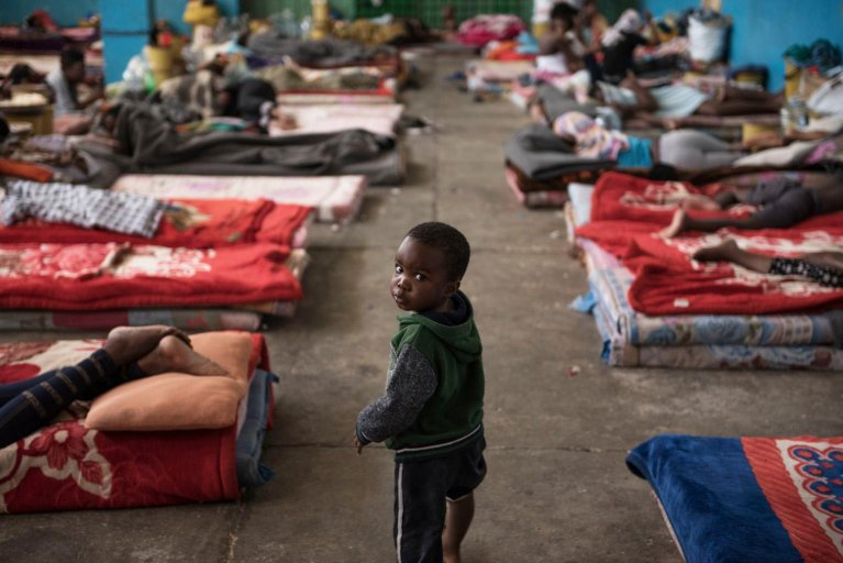 A child walks past mattresses laid on the floor in the women's section of the Al-Nasr detention centre in Zawiya, Libya | Photo: ANSA/UNICEF