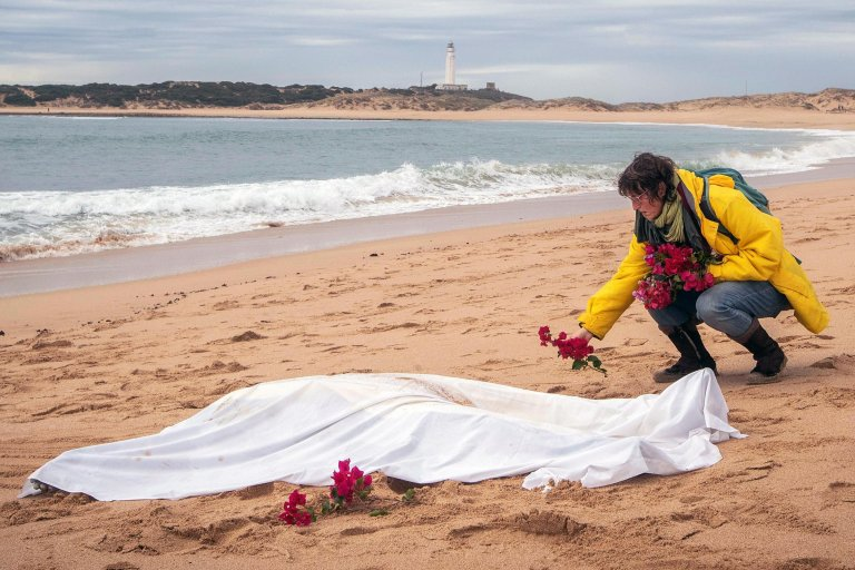 A woman lays flowers around the body of a migrant found in Canos de Meca beach in Cadiz, in southern Spain. Credit: EPA/ROMAN RIOS